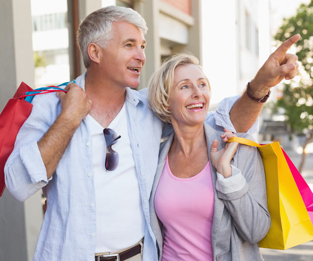 Mature Couple Walking with their Shopping Purchases on a Sunny Day | Platinum Dry Cleaners